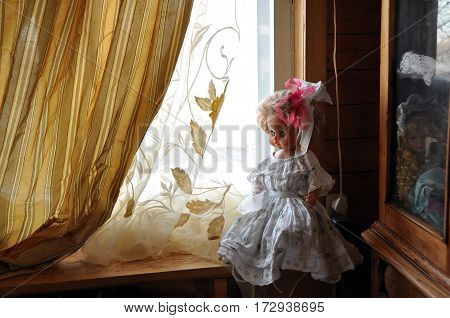 Big doll in a smart white dress and with a bow in her hair on a wooden window sill. Russia
