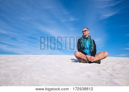 Happy traveler relax among sand dunes on the background of colorful sky. Wonderful travel in the desert.