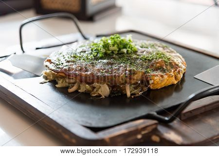 Close up of japanese local food called okonomiyaki or hiroshima pizza cooked by mixed cabbage pork noodle egg and sauce on iron plate in osaka Japan.