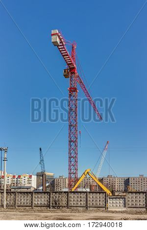 construction site with a high crane behind a fence