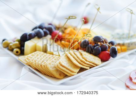 Different Kinds Of Wine Snacks: Cheeses, Crackers, Fruits And Olives On White Table