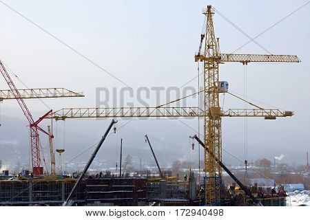 Workers are building a building by means of a tower crane