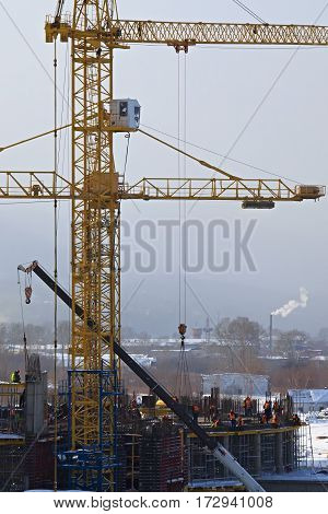 Workers build a building with a crane