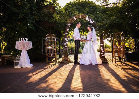 Groom and bride in a white wedding dress on a background of a wedding arch of willow branches. Wedding photography. Arch way