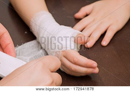 Woman putting bandage on a child's hand