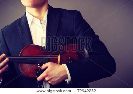 Music passion hobby concept. Man man dressed elegantly holding wooden violin. Studio shot on dark background