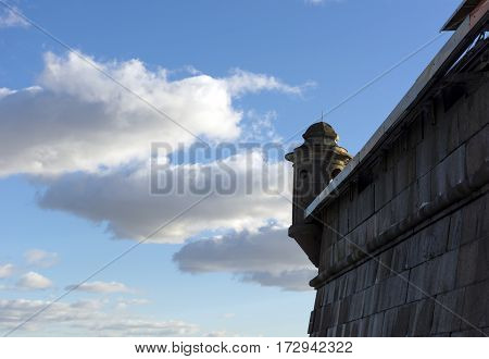 corner tower stone wall of the fortress on a background of blue sky and white clouds Sunny day SaintPetersburg Russia