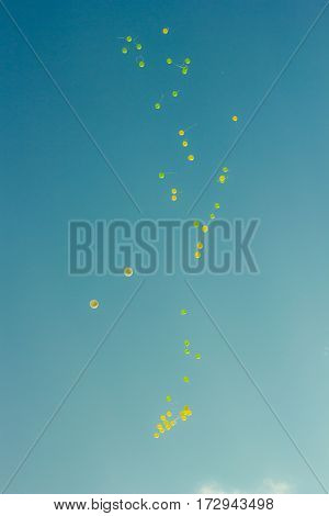Balloons flying on blue sky away from us