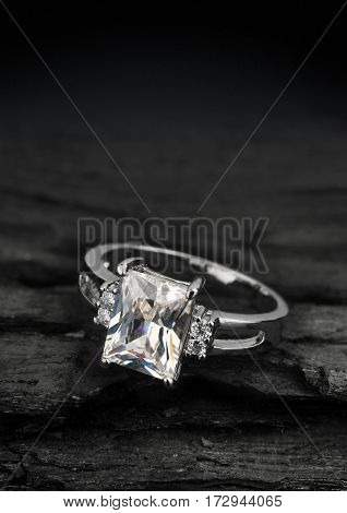 jewellery ring witht diamond on dark coal background
