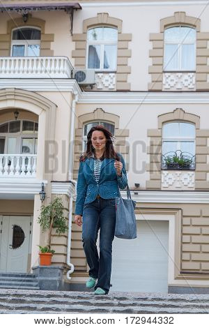 Beautiful lady is near the high-end homes. People