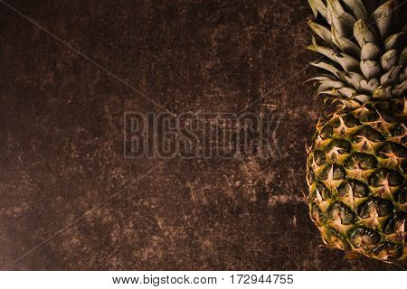 Ripe pineapple lying on a dark marble table. Delicious fruit. Healthy eating. Yellow pineapple on the table