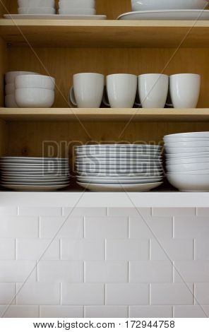 All white dishes in a cupboard with subway tile.