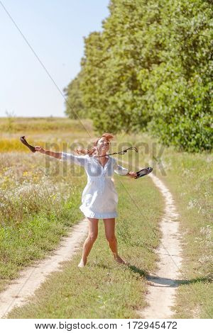 Young beautiful woman running in grass barefoot and holding shoes in hands.