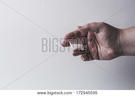 Mans hand holds plastic packet with cocaine powder or another drugs. Drug dealer selling drugs junkie. Free copy space for text