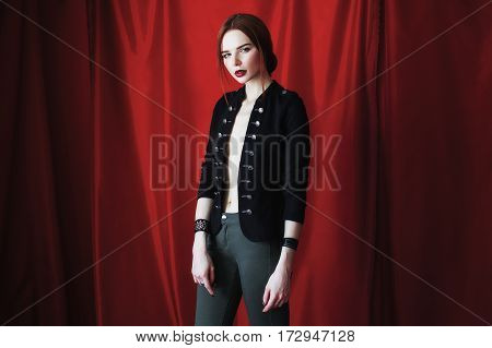 Beautiful red-haired fashion style girl in black unbuttoned jacket with bracelet on hand on red background looking at the camera. Fashion photography. Bright appearance. Red hair. Woman posing hands. Woman style