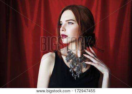 Beautiful redhead woman with parted lips in black dress on red background looking away. Fashion photography. Bright appearance. Red hair. Woman posing hands. Redhead fashion model with necklace