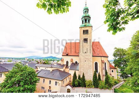 View of old catholic church in salzburg, green and red roof, rainy day, austria