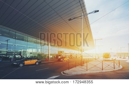 Glass facade of modern contemporary airport terminal in Barcelona with huge ceiling road parking cabstand with yellow taxis and bus waiting passengers stream of people passing rotating doors