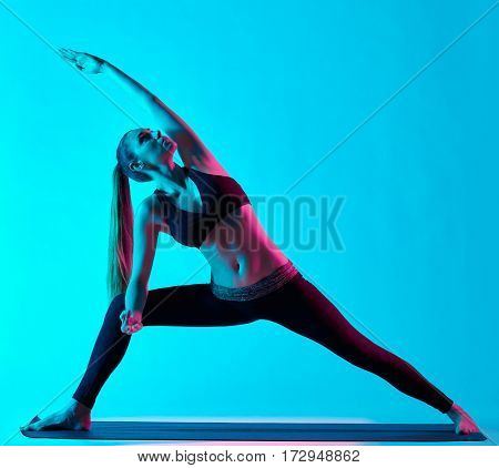 one caucasian woman exercising Utthita Parsvakonasana yoga exercices  in silhouette studio isolated on blue background