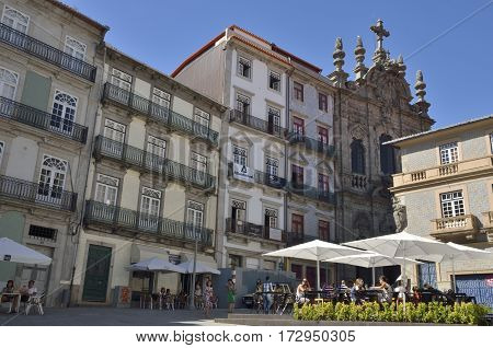 PORTO, PORTUGAL - AUGUST 5, 2015: People at an outdoor restaurant in a plaza near the Ribeira in Porto Portugal.