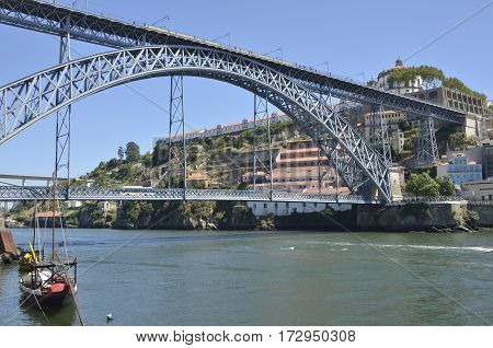 PORTO, PORTUGAL - AUGUST 5, 2015: Traditional wine ship in front of the Bridge of Don Luis over the river Douro in the Porto Portugal.