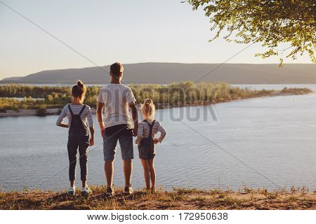 Boy and two little girls standing holding hands looking on horizont.