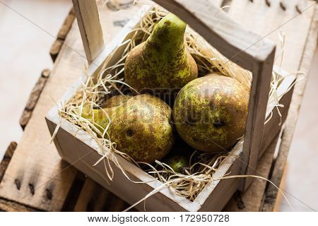 Top view of heap of ripe organic conference pears on straw in aged wood box local produce authentic style kinfolk
