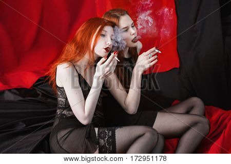 Two red-haired girl hugging and smoke on black and red background. Two lesbian women. Long red hair. Beautiful sexy lingerie transparent. Love between girls. Bad habit to smoke