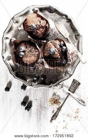 Chocolate cupcake on an antique silver tray with blueberry on the top. Delicious food with nice table-ware. Food concept.