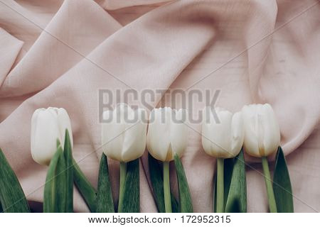 Hello Spring Flat Lay. Stylish White Tulips On Beige Soft Fabric On Rustic  Table Background Top Vie
