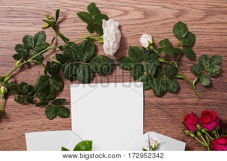 Copyspace on paper. Open envelopes frame of red and white roses and red hearts on wooden background. Greeting card. Conceptual photography. Wedding invitation card. Valentine day. Flat lay top view, copyspace, mock up