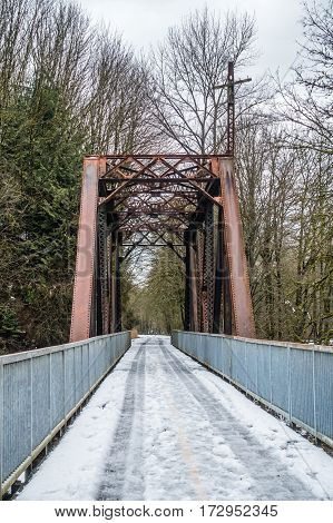 Snow covers a bridge and trestle that spans the Cedar River in Renton Washington.