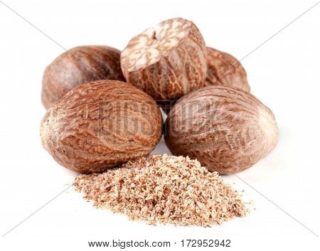 a heap of nutmeg and powder isolated on white background.