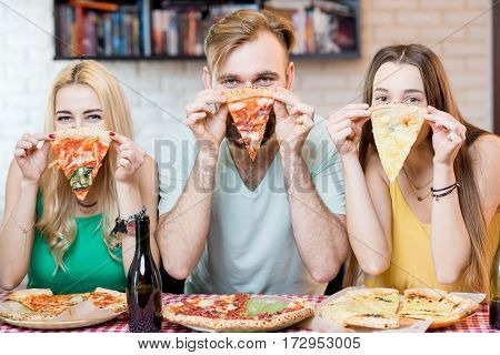 Portrait of young funny friends dressed casually in colorful t-shirts holding slice of pizza at home