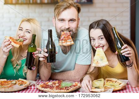 Portrait of young funny friends dressed casually in colorful t-shirts holding slice of pizza and beer at home