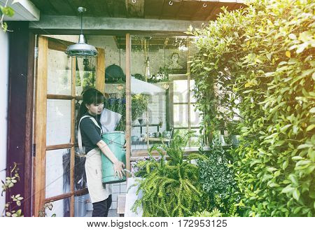 Young florist woman carrying a bucket of flower
