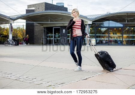 Full length of young woman with wheeled luggage walking outside train station