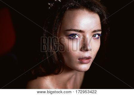 Studio portrait of a beautiful girl with long hair. Glitter on your face. Beautiful eyes. Dark background. Mysterious, mystical,