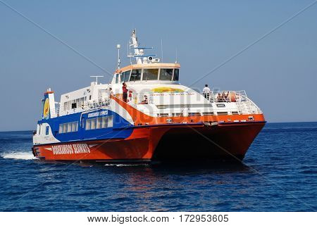 TILOS, GREECE - JULY 19, 2016: Dodekanisos Seaways catamaran ferry Dodekanisos Express arrives at Livadia harbour on the Greek island of Tilos. The 40mtr vessel was built in 2000 in Norway.
