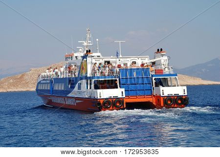 HALKI, GREECE - JULY 19, 2016: Dodekanisos Seaways catamaran ferry Dodekanisos Express departs Emborio harbour on the Greek island of Halki. The 40mtr vessel was built in 2000 in Norway.