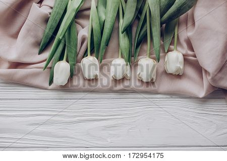 Stylish White Tulips On Beige Soft Fabric And Rustic Wooden Table Background Top View. Hello Spring
