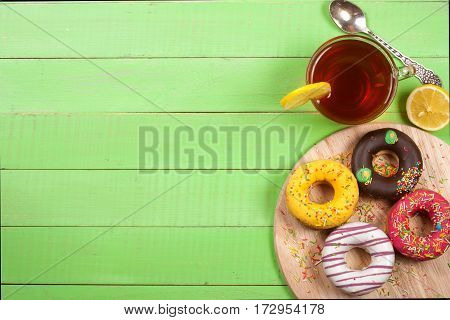 glazed donuts with a cup of tea on a green wooden background with copy space for your text. Top view.