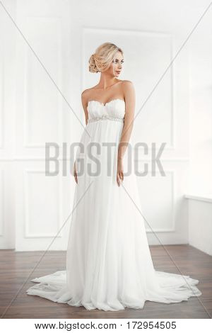 Classical young gourgeous bride. Studio interior fashion shot of fashion model in wedding dress in white room. Blonde woman in full lenght looking away.