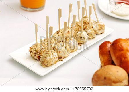 Cheese balls breaded and fried with bamboo sticks. Laid out on a white plate, surrounded by the festive table.