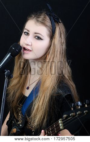 a woman sings a song under a guitar