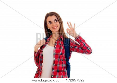 cheerful stylish student girl with backpack on her shoulders smiling and showing OK isolated on white