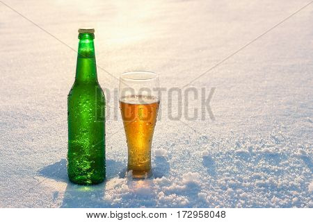 Mug and bottle of cold beer in the snow at sunset. Beautiful winter background. Outdoor recreation. Advertising of alcoholic beverage. Booze and holidays.