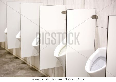 Several white urinals in men's room Urinate