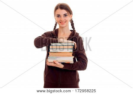 cutie stylish student girl with pigtails in brown sports clothes and books in her hands smiling isolated on white