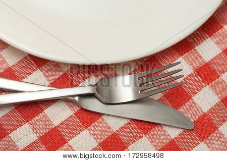 Empty plate with cutlery on checkered tablecloth.